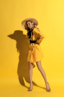 Pretty blonde girl with freckles in yellow outfit and straw hat on yellow background