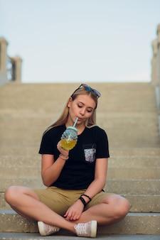 Довольно блондинка с бокалом освежающего лимонада
