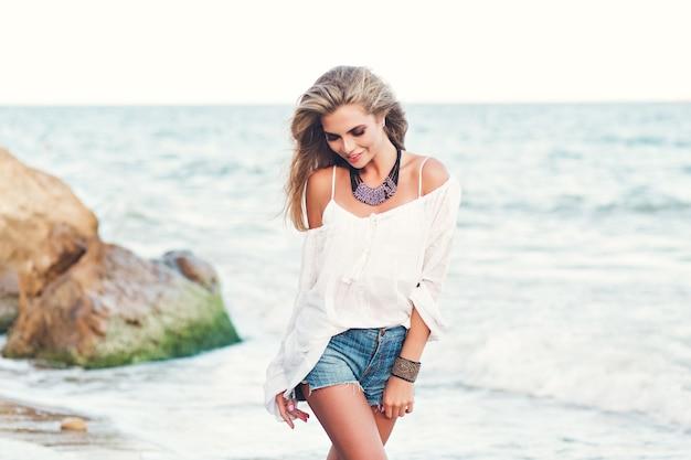 Bella ragazza bionda con i capelli lunghi sta camminando sulla spiaggia vicino al mare. lei sta sorridendo.