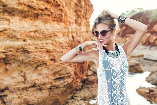 岩の背景にカメラにポーズをとって長い髪のかなりブロンドの女の子。彼女は髪を上に持ち、横を向いています。