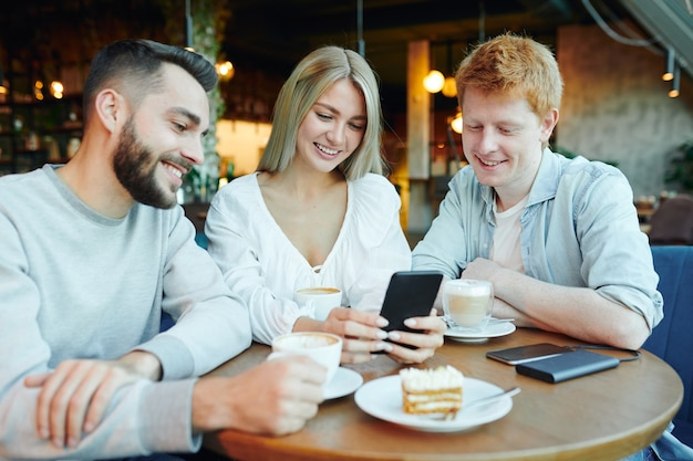 Pretty blonde girl with smartphone showing two happy guys her new photos while relaxing by cup of cappuccino by table in cafe
