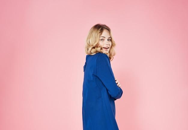 Довольно блондинка в голубом платье на розовом фоне