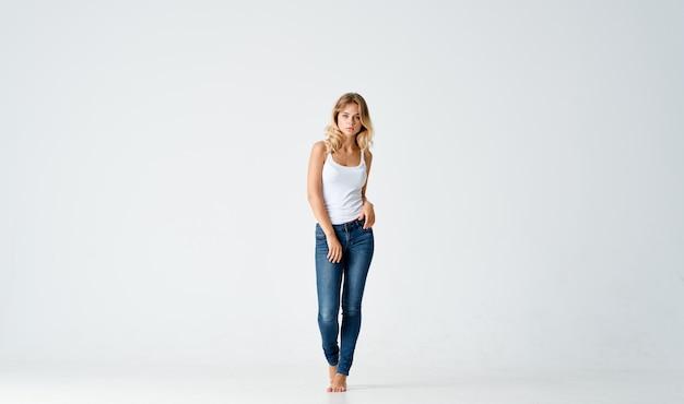 Довольно блондинка в джинсах босиком позирует моды изолированный фон