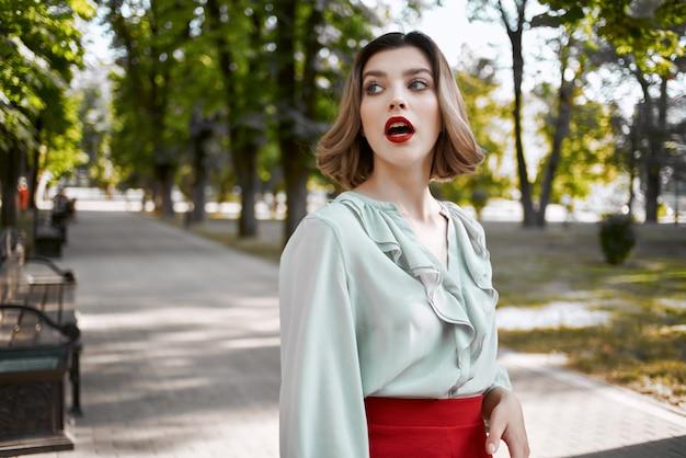 公園の緑の木々の屋外で赤いスカートのきれいな金髪