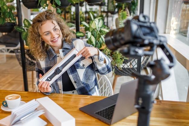 カメラで新製品をテストするかなり金髪のインフルエンサー