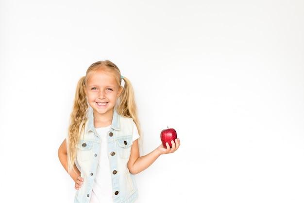 Pretty blonde little girl standing on white holding red apple
