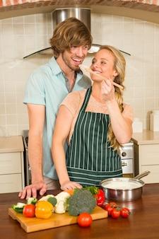 Pretty blonde making her boyfriend taste the preparation in the kitchen