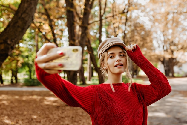 Pretty blonde making selfie in the autumn park. charming lady in red sweater and white hat makes photos.