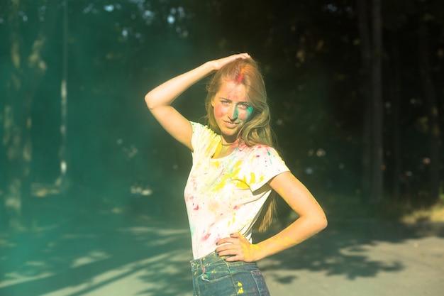 公園で緑のドライペイントホーリーで遊ぶかなり金髪のモデル