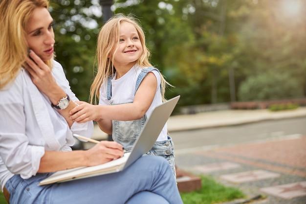 예쁜 금발의 어머니와 푸른 나무의 배경에 공원에서 노트북에서 작업하는 귀여운 딸