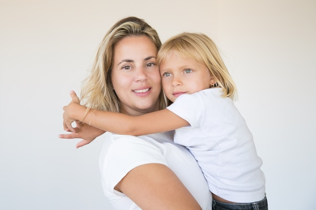 Pretty blonde mother holding daughter and looking at camera
