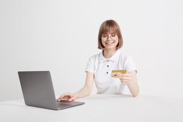 예쁜 금발은 집에 앉아 온라인 상점에서 랩톱에서 온라인 구매를 지불합니다. 신용 카드로 결제