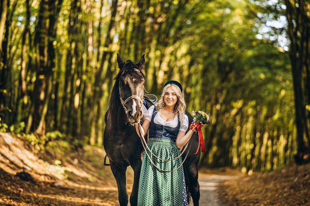 Pretty blonde in traditional dress  walking with big black horse in the forest