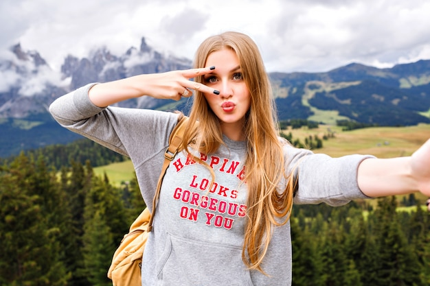 Pretty blonde traveler woman having fun at mountains.
