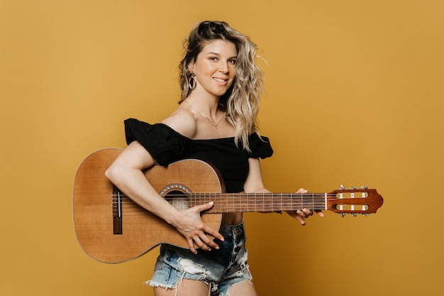 黄色の背景にアコースティックギターをかざすブラックトップとジーンズのショートパンツでかわいい笑顔のきれいな金髪。自宅で練習しているミュージシャン。喜びのための趣味。隔離中は家にいてください。