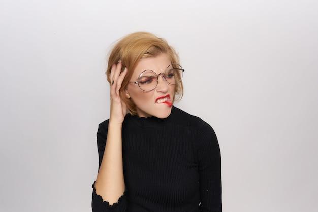 Довольно блондинка в очках в черном свитере эмоции позирует