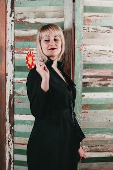 Pretty blonde woman in black dress holding red lollipop