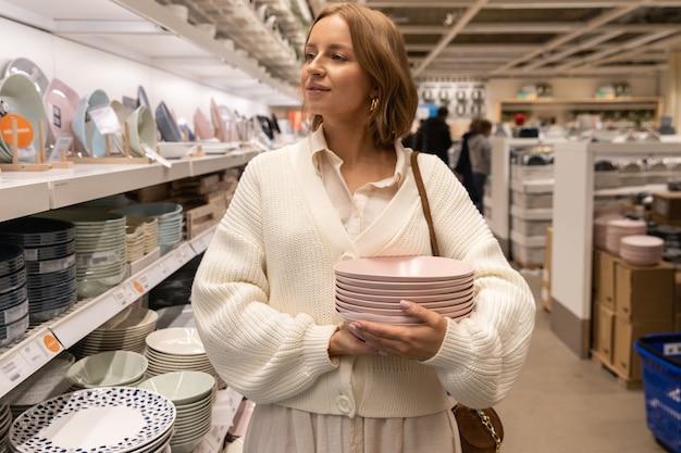 Довольно блондинка клиент выбирает и покупает тарелки из розовой глины