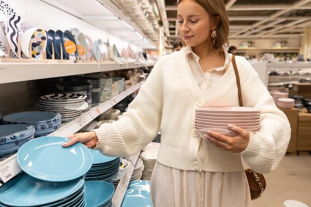 Довольно блондинка клиент выбирает и покупает тарелки из розовой глины Premium Фотографии