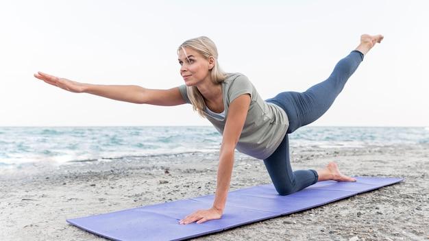 Donna abbastanza bionda che fa yoga in spiaggia