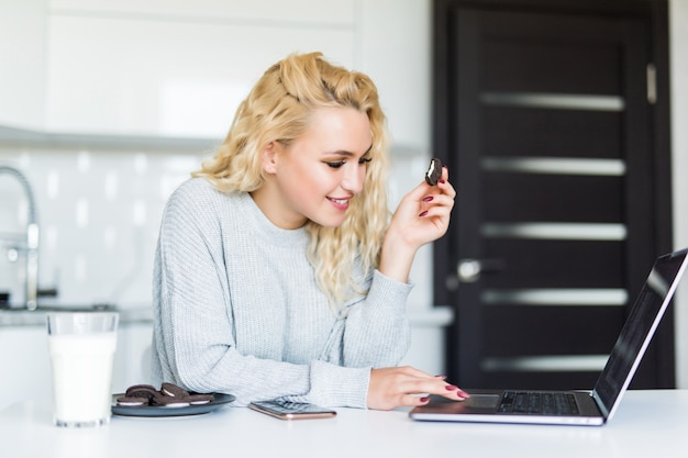 Pretty blonde woman drinking milk from a glass, eating cookies using laptop computer while sitting at the kitchen table