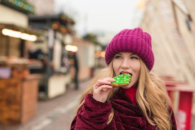 キエフの通りでおいしいクリスマスジンジャーブレッドクッキーを食べるきれいなブロンドの女性