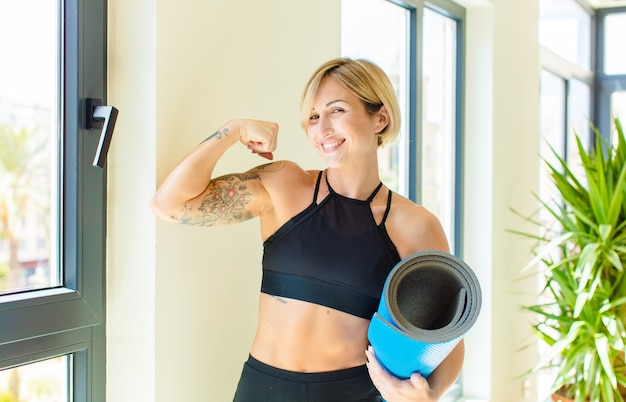 Pretty blonde woman feeling happy, satisfied and powerful, flexing fit and muscular biceps, looking strong after the gym