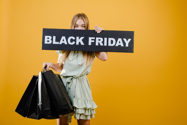 Pretty blonde woman has black friday sign with paper shopping bags isolated over yellow