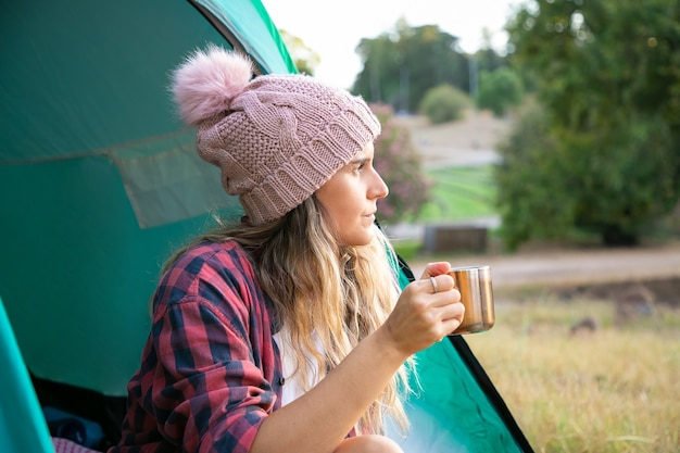 Pretty blonde woman in hat drinking tea, sitting in tent and looking on scenery. caucasian long-haired traveler holding cup or relaxing in park. tourism, trip and vacation concept