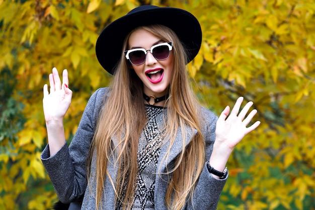 涼しい秋の日に都市公園で楽しんでいるきれいな金髪の女性、エレガントな流行の服、スカーフ、帽子のサングラス、チョーカー、エレガントなストリートスタイル
