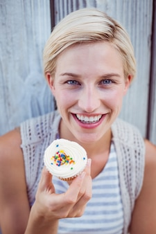 Pretty blonde woman holding cupcake