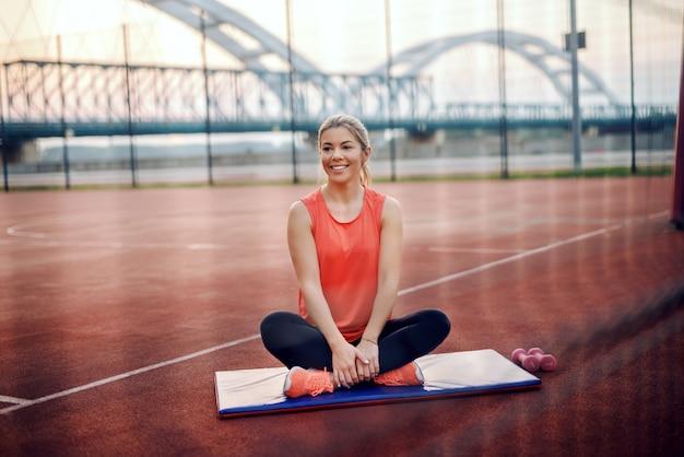 Довольно блондинка в спортивной одежде, сидя на коврике со скрещенными ногами