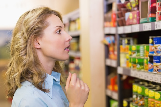 Pretty blonde woman looking at shelves in supermarket