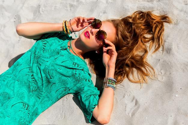 クールなスタイリッシュなサングラス、自由奔放に生きるチュニック、明るい流行のアクセサリーを身に着けている熱帯の太陽が降り注ぐビーチで横になっているかなりブロンドの女性