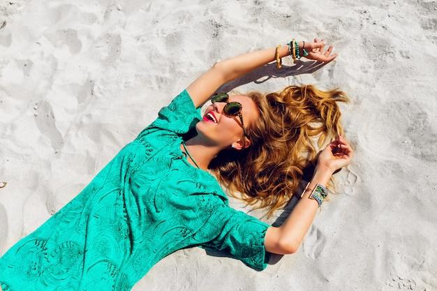 Bella donna bionda sdraiata sulla spiaggia soleggiata tropicale