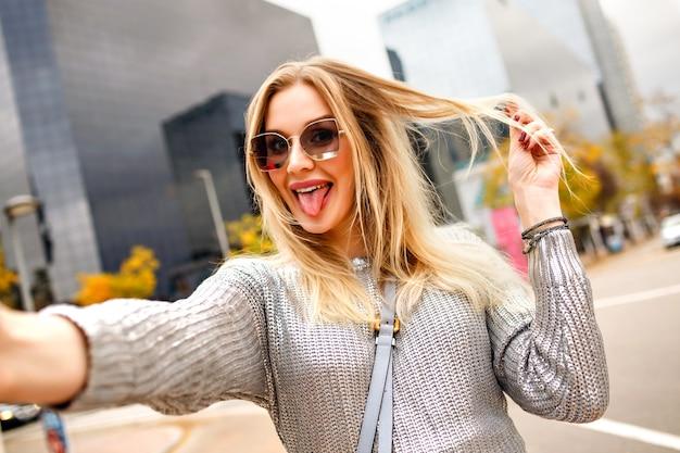 Довольно блондинка делает селфи на улице возле района современных зданий, в сером свитере и гламурных аксессуарах, показывает длинный язык, счастливый турист, позитивное настроение.