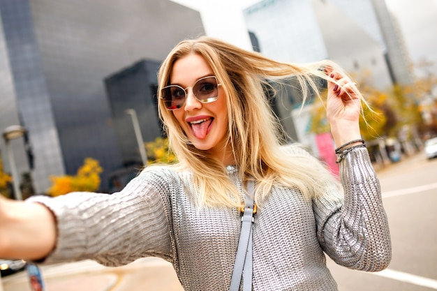 Pretty blonde woman making selfie in the street near modern buildings area, wearing grey sweater and glamorous accessories , showing long tongue, happy tourist, positive mood.