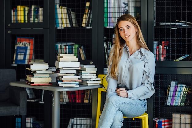 Bella donna bionda o modella seduta nella biblioteca del college con libri sul tavolo, con gli occhiali sulle mani