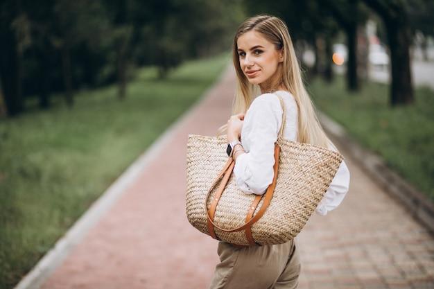 Pretty blonde woman in park wearing summer look