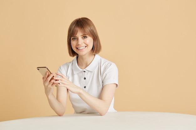 예쁜 금발의 여자는 응용 프로그램에 카드를 추가 한 후 휴대 전화에서 온라인 구매에 대해 지불합니다. 신용 카드 결제