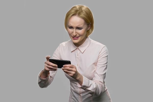 온라인 게임을 예쁜 금발의 여자. 회색 배경에 대해 그녀의 스마트 폰에 비디오 게임을 재미 비즈니스 여자.