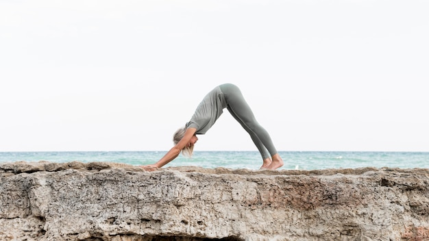 Pretty blonde woman practicing yoga at the beach
