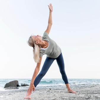 Довольно блондинка упражнениями йоги на открытом воздухе