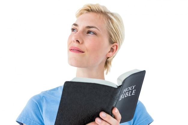 Pretty blonde woman reading bible
