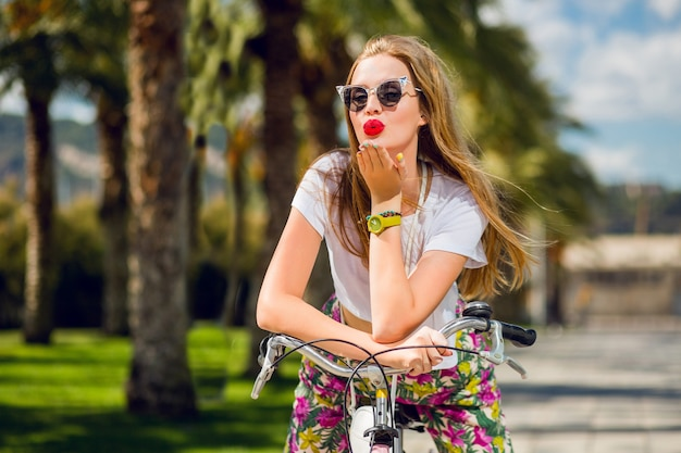 Pretty blonde woman riding bicycle and sending kiss