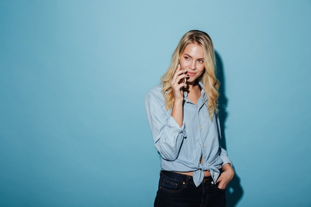 Pretty blonde woman in shirt talking by smartphone