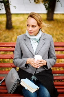 Pretty blonde woman sitting alone on a bench in autumn park with a notebook and cup of drink