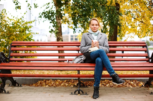 Pretty blonde woman sitting alone on a bench in autumn park