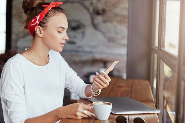 Довольно блондинка сидит в кафе