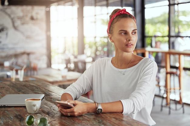 カフェに座っているかなりブロンドの女性